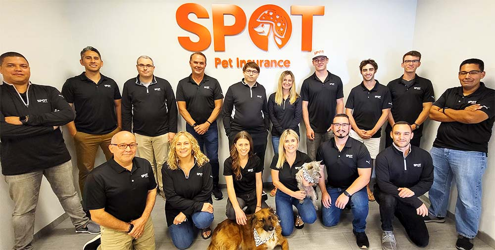 SPOT Employees in front of company logo