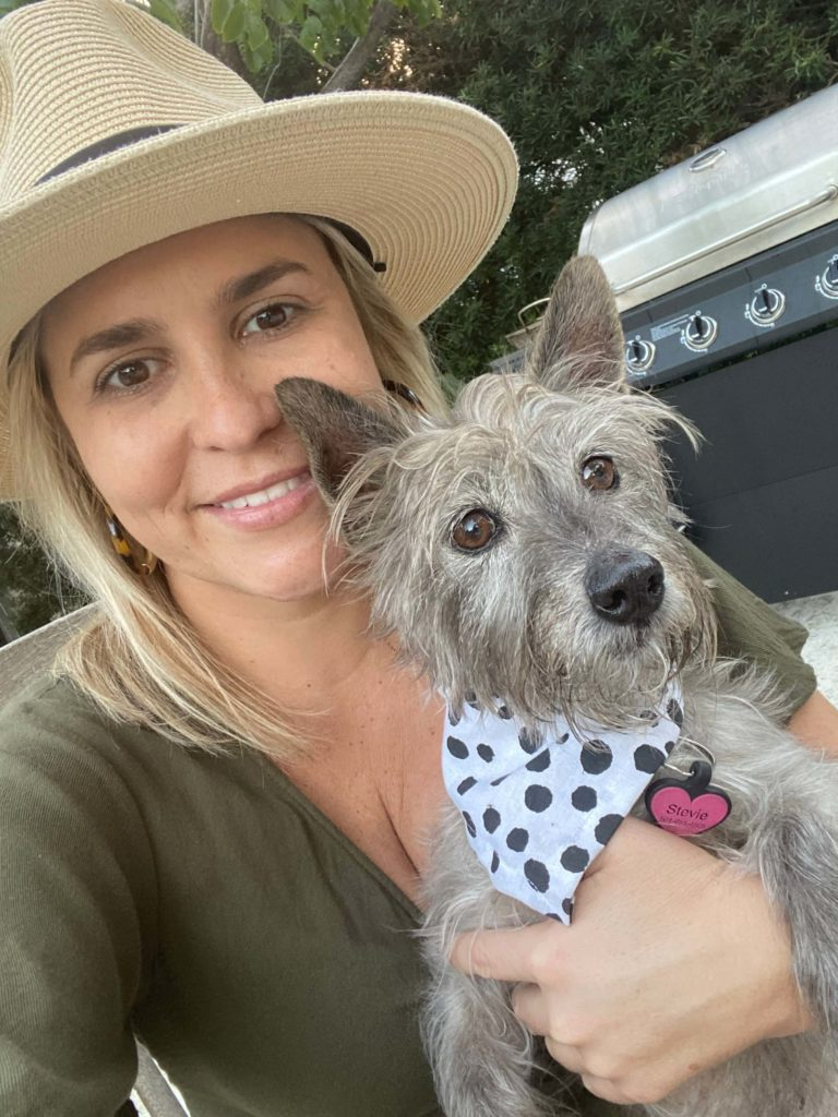 Woman with hat and small dog with spotted bandana